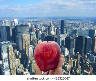 Holding an apple on rooftop of Empire State Tower, New York