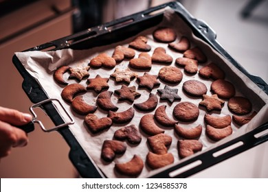 Holding baking tray with burnt gingerbread cookies