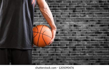Holding Basketball on stone background
