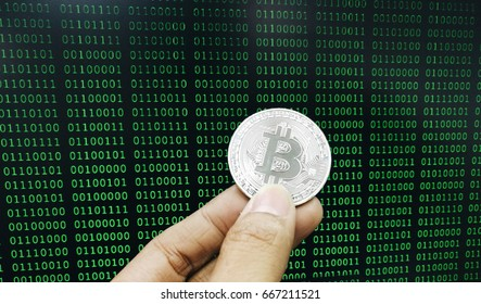 Holding Bitcoin by hand with the background of binary code