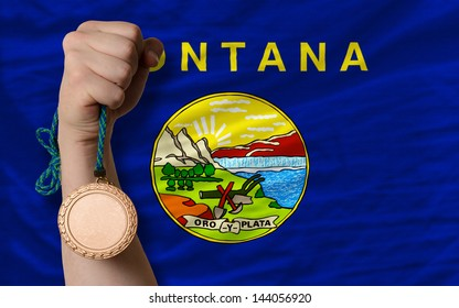 Holding bronze medal for sport and flag of us state of montana