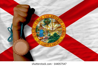 Holding bronze medal for sport and flag of us state of florida