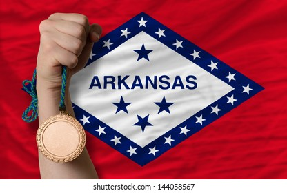 Holding bronze medal for sport and flag of us state of arkansas