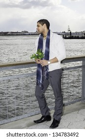 Holding a bunch of green leaves, a young handsome guy is standing by the fence of a river, looking faraway./Waiting for You