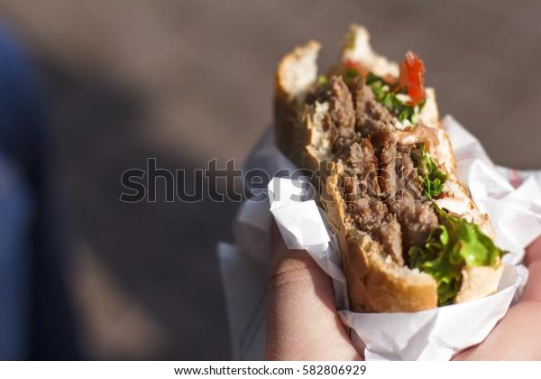 Holding a burger in a hand. Bitten burger. A piece of burger