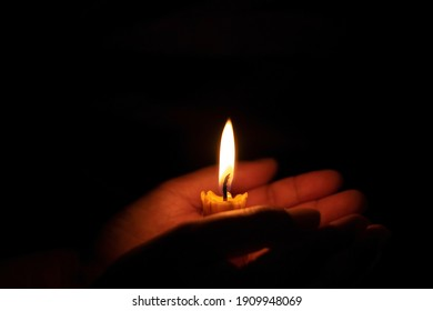 Holding a burning candle in the night