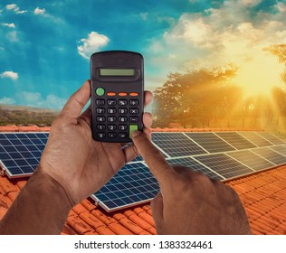 Holding a calculator on a solar panel photovoltaic installation background