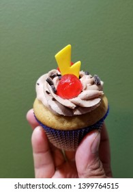 Holding a cappucino cupcake with a yellow candy and a red cherry on top
