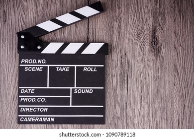 holding clapper board or slate film concept On wooden table.