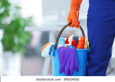 holding cleaning products and tools on bucket, close up