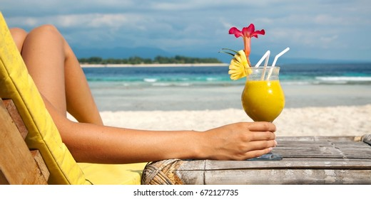 Holding cocktail on a tropical beach