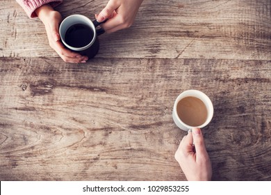 Holding coffee cup, wooden table