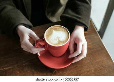 holding a coffee in winter
