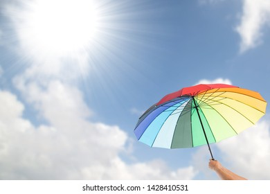 Holding colorful umbrella for protection UV light.