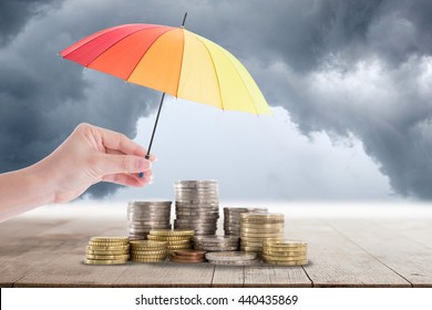 Holding colorful umbrella for saving money. Protection investment concept.