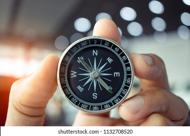 holding compass on tree mountain and sea blurry background. Using wallpaper or background travel or navigator image.