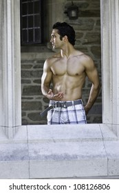 Holding a cross symbol a handsome, muscular guy is standing by a window and  looking around/Looking for light