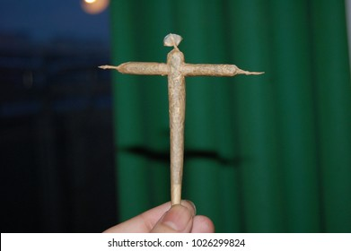 Holding up Crossroads Cannabis Cross Joint