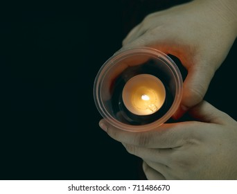 Holding a cup candle isolated in black background