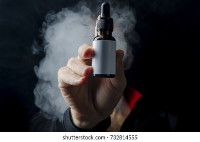holding e liquid bottle for electronic cigarette, isolated ecig flavor bottle for vape devices over a black background.
