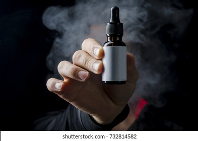 holding e liquid bottle for electronic cigarette, isolated ecig flavor bottle for vape devices over a black background.
