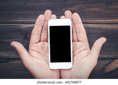 Holding empty copy space smartphone with two hands as it was very precious object. Wooden desks table in the background.