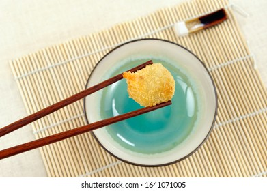 Holding fried Chinese dumpling with chopsticks. ,
