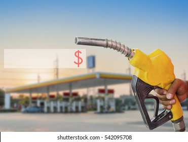 Holding a fuel nozzle against with gas station blurred background.