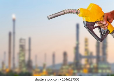Holding a fuel nozzle against with Oil refinery blurred background.