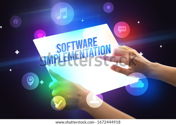 Holding futuristic tablet with SOFTWARE IMPLEMENTATION inscription, new technology concept
