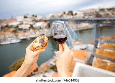 Holding a glass of red wine with traditional portuguese dessert called pastel de Nata on the beautiful cityscape background in Porto, Portugal