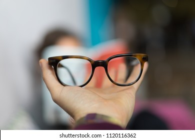 Holding glasses with bokeh in the background