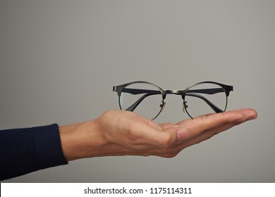 Holding glasses on hand palm close-up isolated on gray background