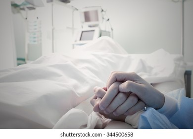 Holding the hand of a dying man in hospital