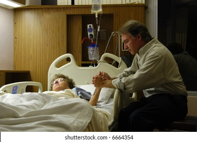 Holding the hand of a sick loved one in the hospital and praying.