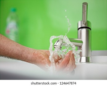 holding hand under sparkling fresh water out of the faucet
