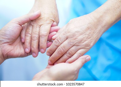 Holding hands Asian senior or elderly old lady woman patient with love, care, encourage and empathy at nursing hospital : healthy strong medical concept