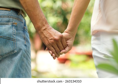 Holding hands of mature couple walking outdoors