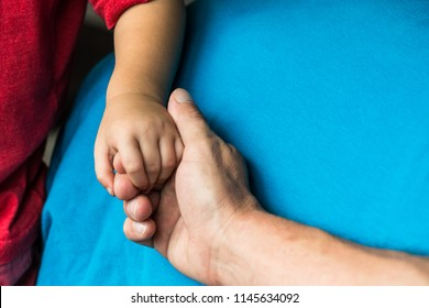Holding hands with my baby boy. My son and daddy holding hands with blue background