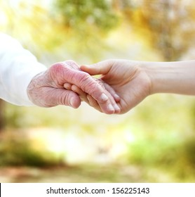 Holding hands with senior on autumn yellow foliage background
