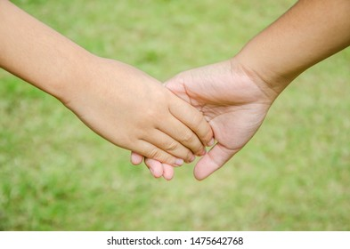 Holding hands together with grass background.