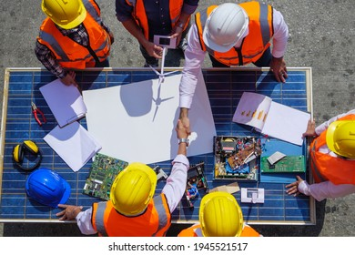 Holding hands top view of Architectural engineers working on solar panel and his blueprints with Solar photovoltaic equipment on construction site. meeting, discussing, designing