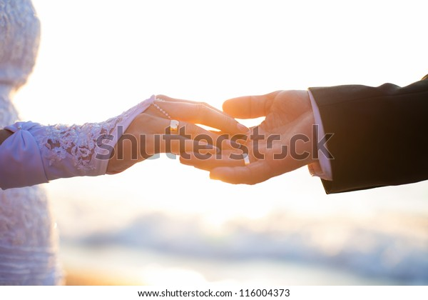 海と日の背景に手と結婚指輪。
