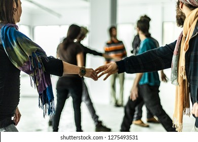 Holding hands while dancing with others. Young people dressed with colorful clothing are dancing together. Closeup pictures on two hands dancing gracefully with blurry people in the background