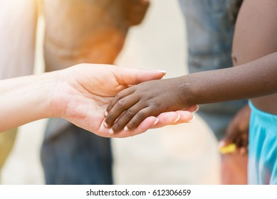 Holding hands.Caucasian woman's hand holding African black little girl's hand.Unrecognizable people, close up
