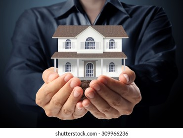holding house representing home ownership and the Real Estate