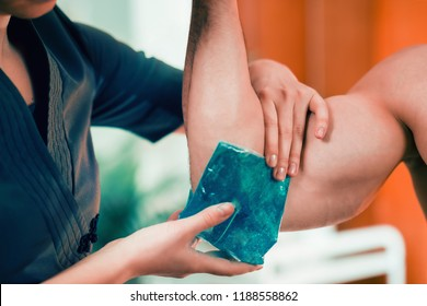 Holding the ice on the painful elbow.