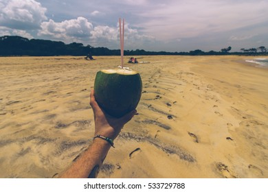 Holding a king coconut on a sandy beach in summer days