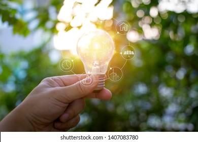 ้hand holding light bulb against nature, icons energy sources for renewable,
