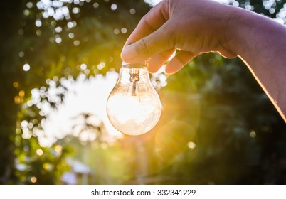 and holding a light bulb with sunset power concept